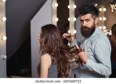 Cute male hairdresser makes haircut a young woman in a beauty salon. Barber or hairdressing salon. Beauty, fashion concept. Girl with long dark hair and hipster with beard, mustache. Barbershop
