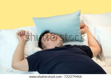 Cute man enjoying dreams while lying on bed / fat man with relaxing