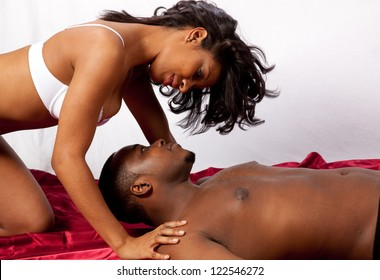 Cute married couple in sexual foreplay together, he is reclining and she is kneeling over his head, in romantic  feeling of love and acceptance