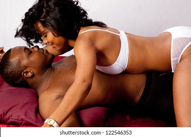 Cute married couple in sexual foreplay together in their underwear, he is supine and she is sitting on him and playfully looking him in the eye while holding his hand out and pinned to the floor