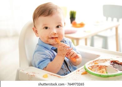 Cute messy baby eating puree at home