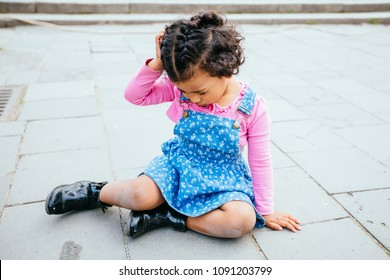 Cute mexican toddler girl fell on park road outdoor in summer time. Child dressed in casual clothing: blue denim sarafan, pink shirt. Dark skinned kid with beautiful dark curly hair.