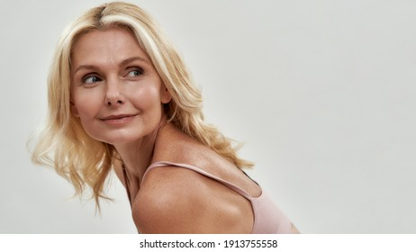 Cute middle aged caucasian woman with fair hair looking at top to side above her shoulder while posing on light background, widescreen. Authentic woman beauty concept