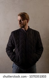 Cute middle-aged bearded man in a black jacket and jeans stands behind the wall looking away. copy space. deadpan without retouching