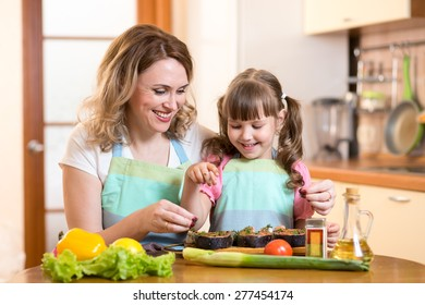 Cute middle-aged woman with child daughter preparing fish in kitchen