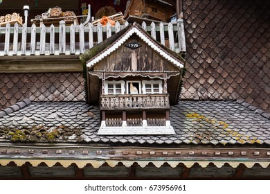 Cute miniature house from 1978 on top of a roof of a house in Malters, Switzerland.