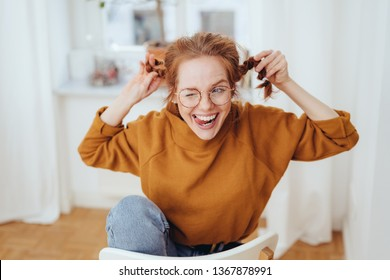 Cute mischievous young redhead woman pulling her pigtails while winking and sticking out her tongue with a teasing expression