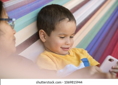 Cute mixed race 2 year old boy plays with a smart phone with colorful background
