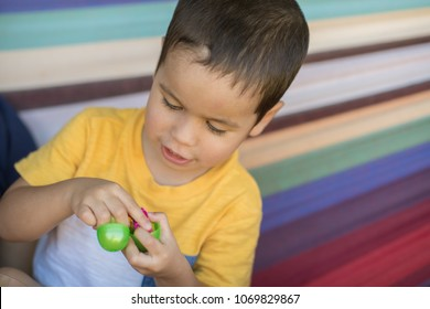 Cute mixed race asian caucasian boy picks candy from a plastic egg