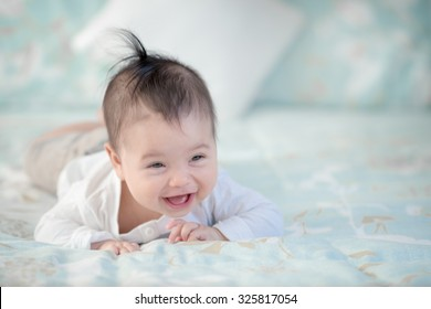 Cute mixed race Asian Caucasian 6 month old baby boy plays inside on a bed