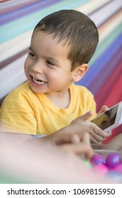 Cute mixed race  boy plays with a smart phone with colorful background