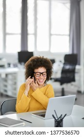 Cute mixed race businesswoman dressed casual sitting in modern office and using smart phone.