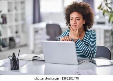Cute mixed race businesswoman dressed  casual thinking how to solve a problem while sitting in modern office.