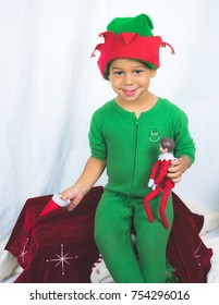 A cute mixed race, caucasian and african american, four year old boy wearing a jingle bell elf hat and onsie posing for a holiday themed children's shoot.