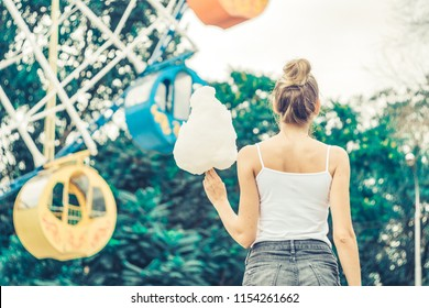 Cute model with cotton candy having fun in the park. Concept of a romantic date and meeting with a girl. Fairy floss as a nice gift. Woman stares dreamily at the Ferris wheel holding cotton candy