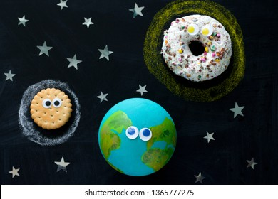 cute model of the Earth, Sun and Moon with googly eyes on the chalkboard, a donut, a globe and a cookie on the chalkboard