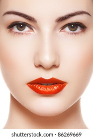 Cute model face with bright evening make-up, orange lipstick, purity skin on white background