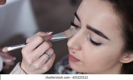 A cute model gets makeup put on before her shoot. Close up shot