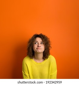 Cute model in yellow sweater among orange background with funny face. Thinking and wondering concepts. Lots of copy space for advertising