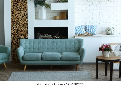 cute modern bedroom interior with blue sofa, fireplace, pot flowers, carpet and table