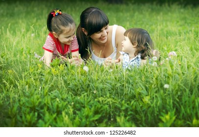 Cute mom and daughters relaxing on the lawn