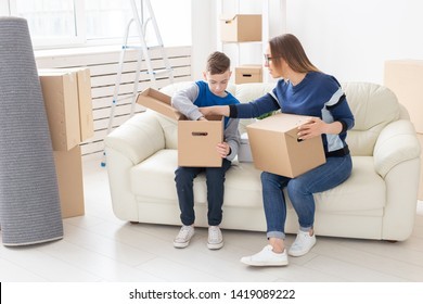 Cute mom and little boy son sort boxes with things after the move. The concept of housewarming mortgage and the joy of new housing.