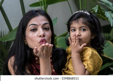 A cute mother and daughter giving flying kiss during a photo session