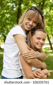 Cute mother and daughter on meadow in park
