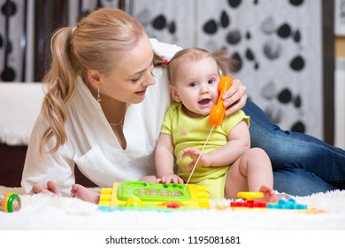 cute mother and kid daughter playing toy phone indoor