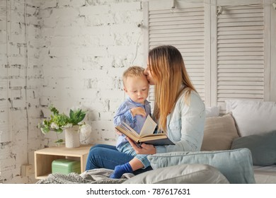 Cute Mother and Son with a Book. Woman and Child Boy at Home