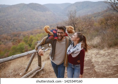 Cute multicultural couple dressed casual hugging and taking a walk in nature with their dog. Man holding dog on shoulders. Autumn season.
