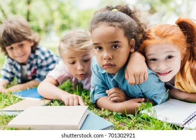 cute multiethnic kids with books lying on grass