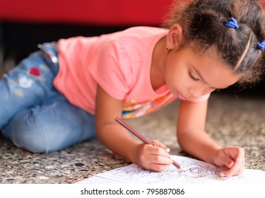 Cute multiracial small girl drawing on a coloring book while lying on the floor