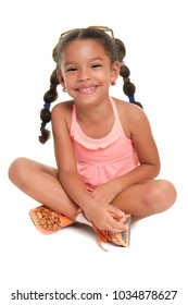 Cute multiracial small girl sitting on the floor and smiling - Isolated on white