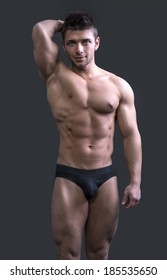 Cute muscular ripped young bodybuilder in bathing suit or underwear, smiling and looking at camera