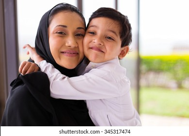cute muslim boy hugging his mother