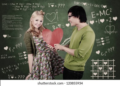 Cute nerd guy is giving his girlfriend Valentine's card in classroom