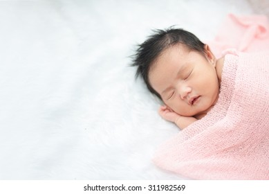 Cute newborn asian girl sleeping on furry cloth wearing roses headband