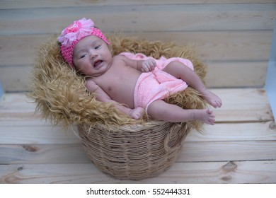 Cute newborn asian girl sleeping in a basket