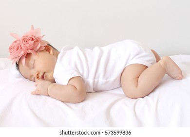 Cute newborn asian girl sleeping and i love you sign hand post on white cloth wearing roses headband.