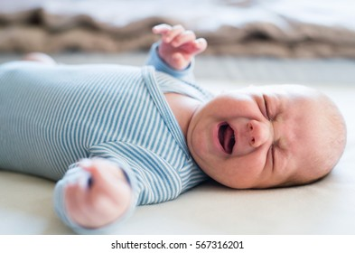 Cute newborn baby boy lying on bed, crying. Close up.