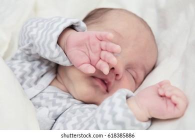 Cute newborn baby boy sleeping, focus on hand
