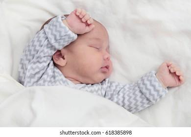 Cute newborn baby boy sleeping, hands up