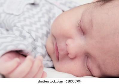 Cute newborn baby boy sleeping, face closeup