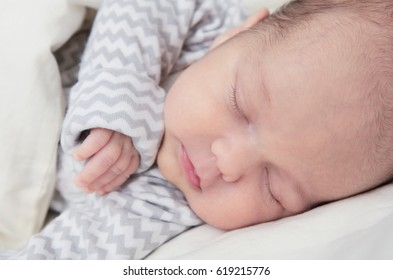 Cute newborn baby boy sleeping, one month old, face closeup