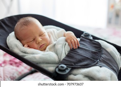 Cute newborn baby boy, sleeping in a swing, covered with blanket, casual clothing