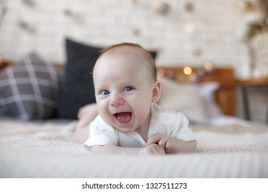 cute newborn baby boy smiling on bed
