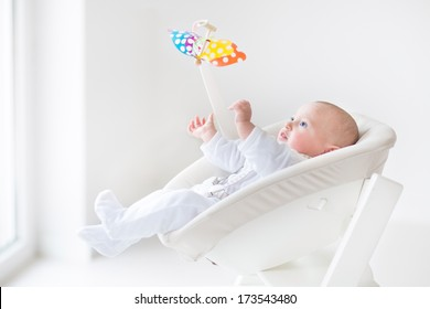 Cute newborn baby boy watching a colorful mobile toy sitting in a white high chair next to a window