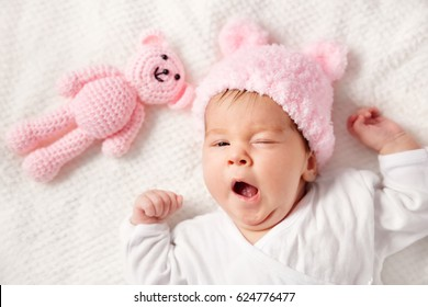 Cute newborn baby girl lying in the bed. Two month old infant child on white soft blanket with teddy bear
