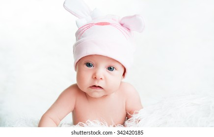 Cute newborn baby girl in a pink hat cap with ears